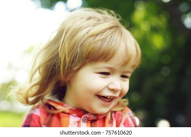 small boy child with happy smiling face and long blonde hair in checkered red shirt on fresh green natural background outdoor