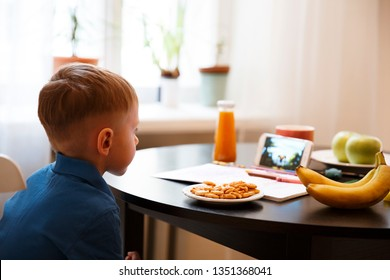 Small boy child sitting at table on chair, watching cartoons on mobile phone screen instead of homework, education and entertainment, digital world, attention loss, serious and concentrated