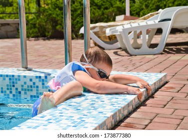 Small boy clambering out of a swimming pool gripping the tiled surround to haul himself up in his buoyancy jacket and goggles