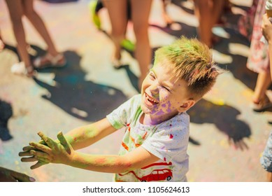Small boy with colorful face portrait in the holi festival. Colorful paint. Festival of paint. Holy. Holi. Child festival. Holiday. Indian children. Smiling