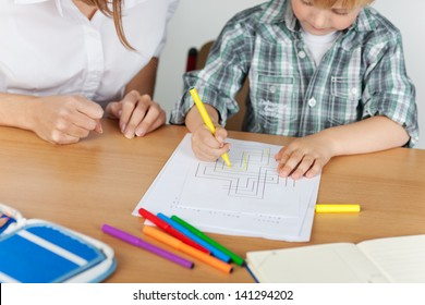 Small boy is coloring during kindergarten with teacher