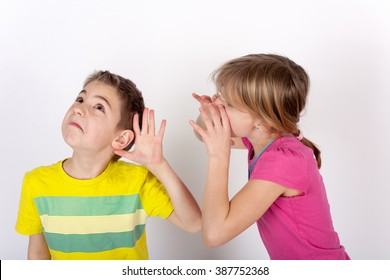 Small boy cupping his hand behind ear cant hear the shouting girl