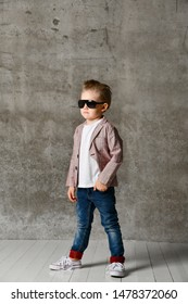 Small boy dandy in light jeans and a stylish jacket, in sunglasses on the background of a concrete wall. Stylish childhood