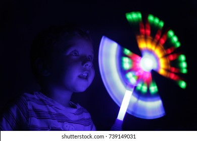A small boy in the darkness enthusiastically looks at a bright glowing toy. Experiment with light and rotation. A boy with a magic wand - a little wizard