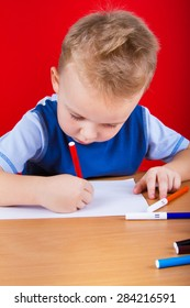 Small boy draws at the table. On a red background