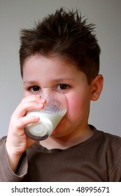 Small boy drinking glass of milk.