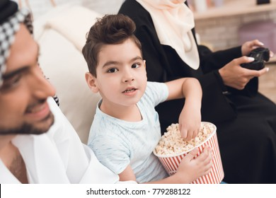 A small boy eats popcorn while his traditional Arab family plays a game console. A man and a woman are sitting on the couch with game joysticks. Happy arabic family concept.