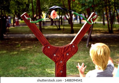 A small boy fired a large projectile from a catapult. The moment of the shot. Attraction in the summer park. Gigantic slingshot.