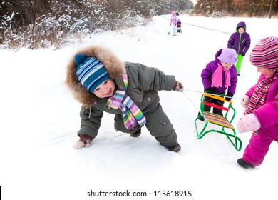 small boy with friends in the snow pulling sled hill