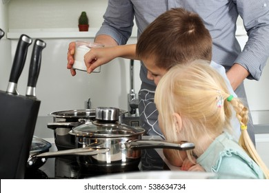 Small boy with girl l salting food with  father in the kitchen