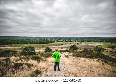 Small boy in a green jacket looking at a dramatic landscape in cludy weather
