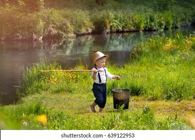 Small boy in a hat with big dog in a field of green grass