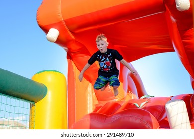 Small boy having fun on a jumping castle leaping in the air as he jumps down from the mouth of a plastic hippo