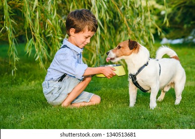 Small boy holding dog bowl in hands to water his thirsty pet dog
