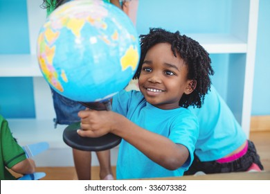 Small boy holding a globe of the world at their desk