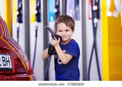 small boy holds a fuel nozzle near the red car