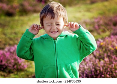 Small boy holds his hands over ears not to hear, making sweet funny face