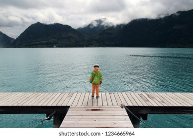 A small boy with a hoodie standing on a pier looking out onto a turquoise lake with mountains and a dramatic sky in the background. Taken at Attersee, Austria.