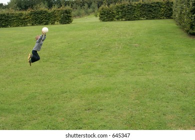 Small Boy jumping in air to catch ball