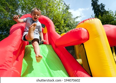 Small boy jumping down the slide on an inflatable bouncy castle