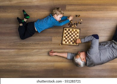 Small boy laying on the wooden floor and playing chess with his grandfather.