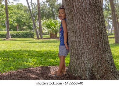 A small boy leans with his back on a large tree laughing out loud. On a hot summer day, kids enjoy playing under a tree shade at the park.