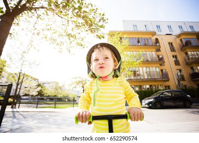 small boy learning to ride scooter on street on sunny day. active outdoors activity for kids. close up portrait of laughing toddler wearing safety helmet riding push bicycle