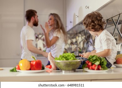 Small boy looking at his parents conflict. Modern white kitchen location.