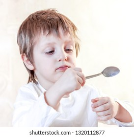 small boy looking into the spoon and eating sweet homemade chokolate dessert