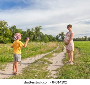 Small boy making soap bubbles with his regnant mother in the green field