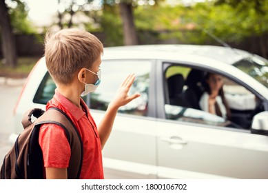 Small boy in medical mask waving goodbye to his mother in the car before having classes in school. Concept of going to school during the coronavirus epidemic