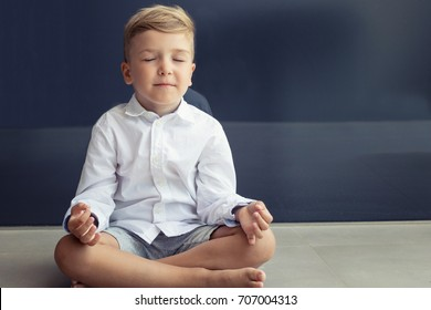 Small boy meditating in lotus position. Child practicing Yoga with eyes closed.