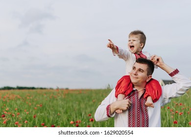Small Boy on Father Shoulders Walking on Field. Happy Mood Smiling Child Son Pointing with Finger Daddy Man. Characters Wearing Ukraine National Suits. Poppy and Cloudy Sky on Background