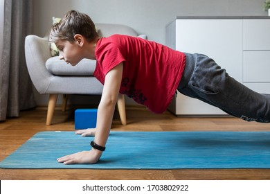 Small boy on yoga mat at home holding plank pose. Child physical activity at home on quarantine