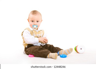 small boy with pacifier plays on the floor