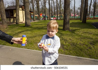 Small boy in the park is trying to make bubble