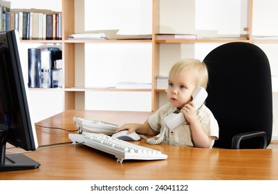 Small boy with phone and computer in office