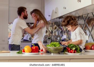 Small boy with the phone in his hands sitting on the kitchen surface while his parents fighting on the background.