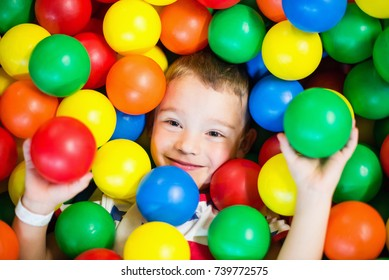 Small boy in a pit full of colorful plastic balls