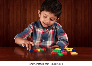 A small boy playing with alphabets