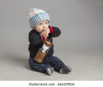 Small boy playing with metal lantern isolated inside studio