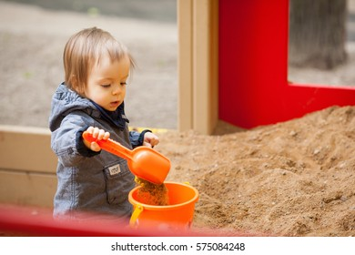 Small boy playing in a sandbox. Portrait of 2 year old toddler with blond hair and blue eyes.