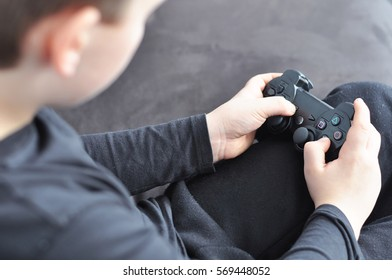 Small boy playing video games. Focus on his hands with the remote control.