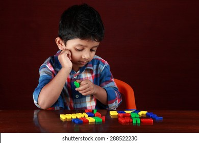 A small boy plays with toy alphabets in a dark background