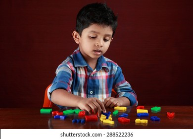 A small boy plays with toy alphabets in dark background