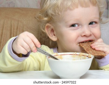 The Small boy with pleasure eats the apple puree.
