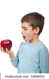 Small boy preparing to bite a big red apple and standing in semi profile isolated on white background