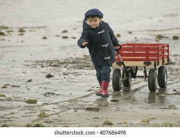 small boy pulling his big red wagon across the ocean beach sand.