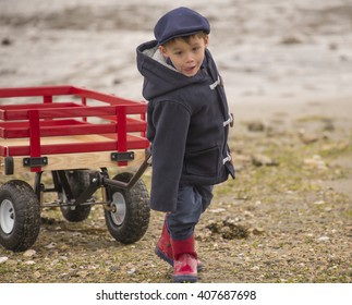 small boy pulling his big red wooden wagon across the rocky, sandy ocean beach.