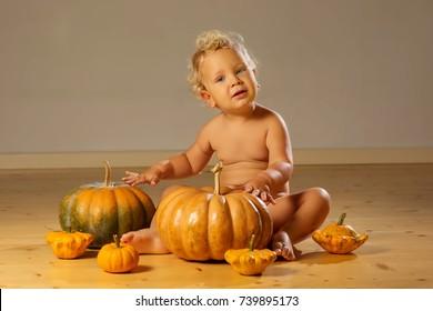 Small boy with pumpkins around posing at studio